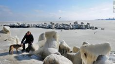 A man pets a dog next to frozen sea waters in Constanta, Romania, on Wednesday, February 1. Temperatures plunged to -34 degrees Celsius (-29 degrees Fahrenheit) in central Romania, where eight people died due to cold-related causes, according to local media.