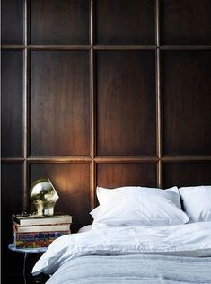 Wood detailed walls in masculine bedroom with modern light and cozy pale blue bedding
