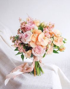 Wedding bouquet of pink and peach garden roses and orchids // Most Popular Bridal Bouquets {Facebook and Instagram: The Wedding Scoop}