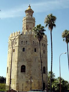 Seville - Torre del Oro © Robert Bovington  The Torre del Oro is a 13th-century Moorish watchtower. There are varying opinions as to how it this dodecahedral tower got its name. Some say that the tower was originally adorned with gold leaf; others say that it was used as a warehouse to store gold from the New World expeditions. Perhaps a simpler explanation is that it is golden in colour!