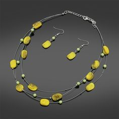 """Triple Strand Necklace Set      Vibrant Yellow stone bead necklace set  In a triple strand design  Perfect to wear day or night  Add A touch of elegant colour to any outfit    Necklace     Polished Yellow Stone set beads    4mm Gold Acrylic spacer beads    In a triple layer wire design    18"""" in length finished with lobster clasp fastening & extension chain    Earrings    Matching Yellow stone set    with gold acrylic beading  In a drop dangle design  with alloy hooks and comfort stoppers…"""