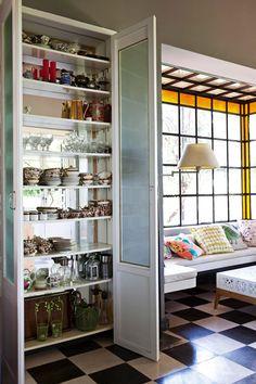 Cocina campestre y moderna con gran ventanal de vidrio repartido, sillón tipo inglés blanco y un armario con fondo espejado para vajilla. Piso en damero blanco y negro.