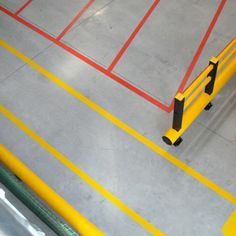 Line marking used to create a walkway and hazard marking in conjunction with a warehouse safety barrier.