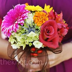 The bridesmaids' colorful arrangements of flowers and berries popped against their vivid dresses. Amber let each maid pick her own style of dress in alternating colors of sangria, watermelon, and champagne.