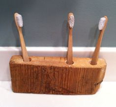 A repurposed wood holder, sanded and finished to hold 2-4 toothbrushes.