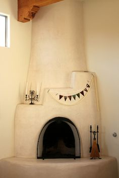 Adobe fireplace/ multiple-strand bunting in the corner Adobe Fireplace, Stucco Fireplace, Fireplaces, Earthship, Southwest Style, Outdoor Spaces, Modern Farmhouse, Sweet Home, Rustic