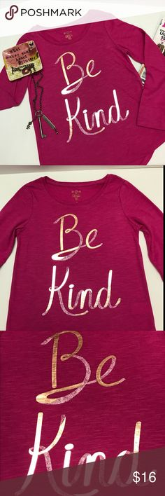 """Be Kind Long Sleeve Tee for Girls These tee are in a pretty shade of fuchsia with a wonderful reminder to """"Be Kind"""" to others that is written in script on the front.  The letters are in a combination of gold foil and white.  The white looks sort of like it was written in chalk.  The top is made of a 60/40 cotton poly blend so it will wash & wear great.  The top also has a hi-lo hem.  Great top by itself or for layering.  NWT Shirts & Tops Tees - Long Sleeve"""