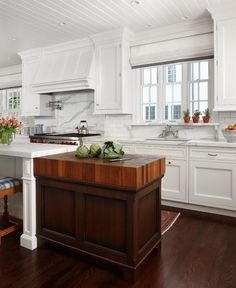 Kitchen: Dark wood floors and island mixed with white walls, cupboards and island
