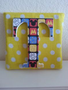Mickey mouse themed wooden letter on fabric covered canvas.