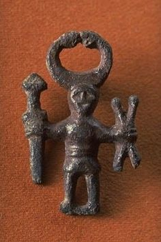Ancient bronze figure compare to God Hermes because of the horns - found in Kungsängen in Sweden - figure has high horned hat and crossed sticks, Bronze Age - at the Historiska Museum, Stockholm
