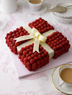Jewel Box Cake from The Great British Bake Off: How to Turn Everyday Bakes into Showstoppers cookbook. This is a square white chocolate sponge cake, completely covered with small raspberries and decorated with white chocolate ribbons, tied to look like a beautiful jewel box.