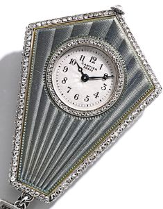 Platinum, Enamel and Diamond Pendant-Watch, Cartier, Paris The circular dial with Arabic numeral indicators, within an elongated hexagon-shaped case applied with steel gray-hued guilloche enamel, the reverse of the case decorated with scrollwork flourishes, set with a pear-shaped diamond weighing approximately .70 carat, accented by old European and single-cut diamonds weighing approximately .85 carat, further set with rose-cut diamonds, the dial, caseback and movement signed Cartier Paris…