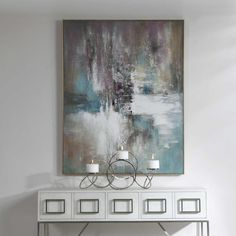Our Elevation Abstract Art Painint exhibits an array of color including lavender, aqua, white, and tan. A gold leaf gallery frame completes the abstract piece, which may be hung horizontal or vertical. Designed by Carolyn Kinder International for Uttermost Company.