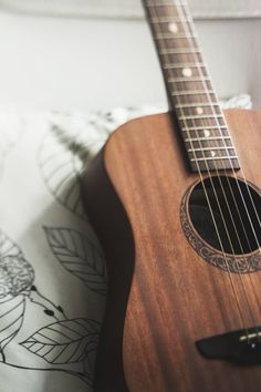 Shallow Focus Photography of Brown Acoustic Guitar on White and Black Leaf Print Pillow Ukulele, Acoustic Guitar Chords, Guitar Songs, Acoustic Guitar Photography, Guitar Photos, Focus Photography, Guitar Accessories, Music Aesthetic, Music Wallpaper