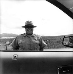 Lee Friedlander photograph of a police officer with a hat framed by the side window of a car
