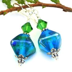 The rich, glowing color of the ENCHANTED AQUA handmade lampwork earrings almost takes your breath away in its dreamlike beauty. The four sided, diamond shaped lampwork beads used to create the unique earrings were individually handmade by glass artist Charlotte of Covergirlbeads.