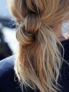 split your ponytail into two and knot it, backcomb the tail with your fingers and pull out a few pieces around your face for a messy, casual look