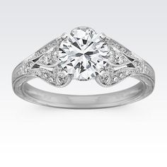 Thirty round pavé-set diamonds, at approximately .34 carat total weight, serve as accents to the center diamond of your choice in this elegant vintage-inspired cathedral engagement ring. Each stone has been hand-selected for fire and sparkle, and is set in superior quality 14 karat white gold with milgrain and engraved side detailing.
