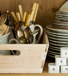 Create a silverware caddy with a basic wood tray and a collection of small pitchers. More storage ideas: http://www.bhg.com/kitchen/storage/organization/affordable-kitchen-storage-ideas/?socsrc=bhgpin062312#page=1