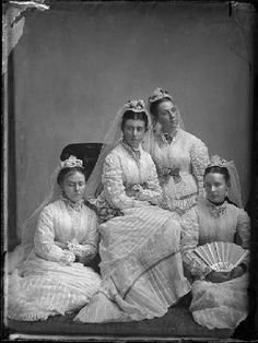 Bridesmaids in Victorian dress pose in a studio setting.
