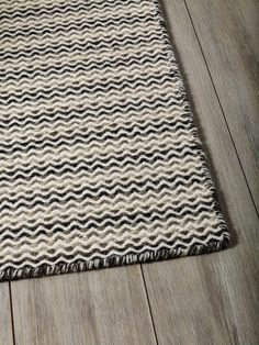 A wave design of four multi-coloured stripes on a soft neutral backdrop that creates a delicate ripple pattern. A durable flatweave rug, made from 100% wool