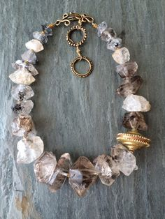 Would love something like this as a bracelet. Neutral colors, antique accents, raw cut stones.