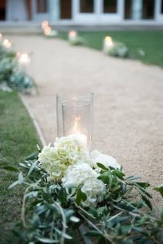 Aisle detail, so pretty and unexpected to place a few flowers on the ground surrounding the hurricane lamps. Not just for weddings. -Deborah Jaffe