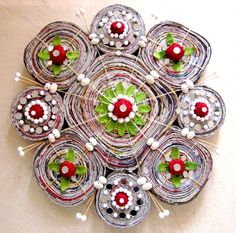 This wall art piece is made of newspaper, decorated with thermocol balls, mirrors, white shells & other decorative things.