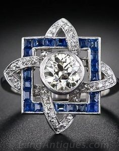 1.00 Carat Diamond and Sapphire Art Deco Ring. Multi-dimensional, 1930s vintage Art Deco diamond ring with a futuristic geometric design, foreshadowing the Atomic symbol of the 1950s. A shining 1.00 carat European-cut diamond 'radiates' from the centre of a square calibré sapphire frame entwined with ribbons of sparkling round diamonds.