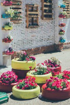 jardin vertical hecho con palets y materiales reciclables, como botellas , bidones, y ruedas, es un jardín sostenible en el colegio