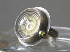 Ring | Tessa Rickard.  Sterling silver, peridot and handmade glass spiral bead.