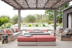 String lights hang from the pergola with a bamboo roof creating an intimate outdoor living area. Peach and rose colored cushions pop against gray tones in this space.