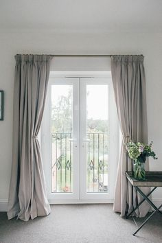 Full length grey curtains on french doors with balcony overlooking a garden.