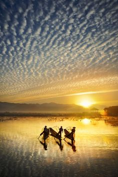 Early one morning on Inle Lake, Myanmar, Burmese fishermen are out on the water to catch fish. by David Lazar