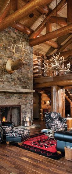 Handcrafted rustic log home by M.T.N. Design. Love the huge fireplace and western decor.