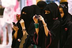Veiled beauty: Arabian women in face-covering niqab snap photos of their children during an Independence Day celebration in Riyadh, Saudi Arabia, in September.    Fahad Shadeed/Reuters