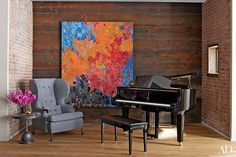 In an alcove off the living area, a Lynne Mapp Drexler painting makes a splash against a wall of reclaimed wood; the piano is by Yamaha, and the wing chair and bronze side table are by BDDW.
