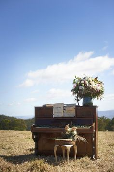 oversized bunch of wildflowers + antique piano....  via Kara & Tim's Rustic Country Lodge Wedding on The LANE. (PS - follow us on instagram! the_lane)