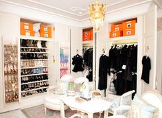 Suzanne Rogers - French closet features floor to ceiling, built-in wardrobe cabinets filled with slanted shoe racks and orange storage boxes situated behind French chairs and French table atop French rug.