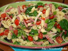 1 Lb box Rottini Pasta. 1 Cup Grape tomatoes, halved. 1 (15 oz) can Black pitted Olives. ½ Lb Hard Salami, cut into small cubes or strips. 1 Cup fresh baby Spinach leaves. 1 (8 oz) package sliced mushrooms. ½ Lb White or Yellow Cheddar, cut into small cubes. 3 Tbls Fresh Basil leaves, chopped. ½ Tsp Red Pepper flakes. Dressing: 2 Cloves fresh Garlic, minced. 3 Tbls Extra Virgin Olive Oil. Juice of 1 Lemon. 1 (12 ozs) Bottle Italian salad dressing of your choice.  Salt and Pepper to taste.