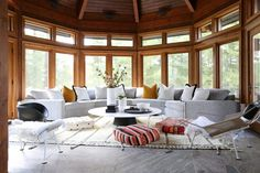 The Muskoka room's panoramic windows give guests the feeling of being outside while they lounge on a custom curved grey sofa that hugs the room's curved walls. Outdoor Furniture Sets, Outdoor Decor, Elle Decor, Service Design, Cottage, Patio, Dining, Living Rooms, Minimalist Home