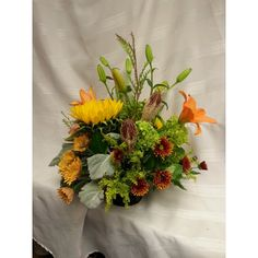 Fall centerpiece of lilies, green hydrangea,sunflowers. dusty miller, bronze poms.  Perfect for any fall  celebration.