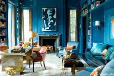Walls in custom peacock-blue lacquer by Fine Paints of Europe give depth and richness to the library of the Oppenheimer's Chicago townhouse designed by Steven Gambrel.  The abstract painting is from Showplace Antique & Design Center. The desk and coffee table are 1960s French pieces- curtains are End Paper from Stark.