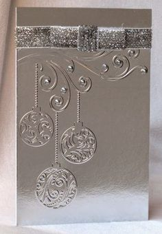 handmade Christmas card ... no color ... all metallic silver ... embossing folder Christmas baubles hanging from flourishes ... silver ribbon wrap and flat bow ... shiny mettallic silver cardstock ... luv it!