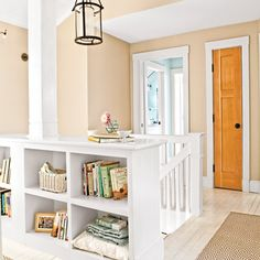 Built-in shelves hold books, photos, and extra blankets on this stair landing | Photo: Keller + Keller | thisoldhouse.com