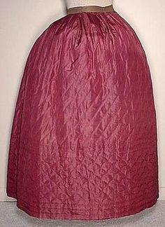 """A most impressive original circa 1850's to 1860's woman's rich burgandy silk satin Winter petticoat that is hand quilted on the diagonal, with a deep bordered clam shell quilted hem. A directionally box pleated waist to the brown sarcenet waistband, and a back hook and eye closure. Lightly batted, with a cotton check lining and a turned hem. A 26"""" waist and 38"""" from waist to front hem. In very good clean sound condition, with no splits, tears or mends, only some very tiny scattered age…"""