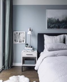 Grey And Blueish Bedroom With A White Bedside Table And A Large Dark Bed.  Beautiful And Elegant Interior Design With A Fur In Front Of The Bed.