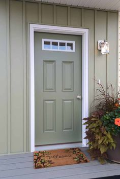 Sage front door. white trim ;siding colored like stucco