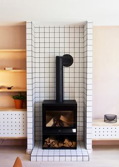 Taking basic white tiles to the next level with this minimal, modern fireplace surround. Want more alternative tiling ideas? Click through for 7 unique and refreshing ways to use wall tiles. #tiling #tilework #interiors #minimal #uniquetilework