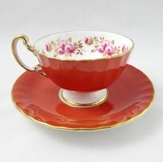 Orange tea cup and saucer made by Aynsley. On the inside rim of the teacup there is a border of pink roses. Gold trimming on the edges of tea cup and saucer and on the handle. Excellent condition (see photos). Markings read: Est 1775 Aynsley England Bone China For more Aynsley tea